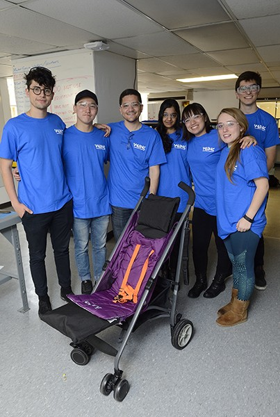 Engineering students in blue shirts pose next to the stroller they designed and built