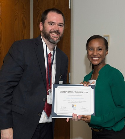 A program director and graduating student pose with the student's diploma