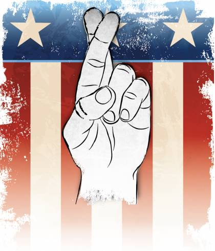 Crossed fingers in front of an American flag