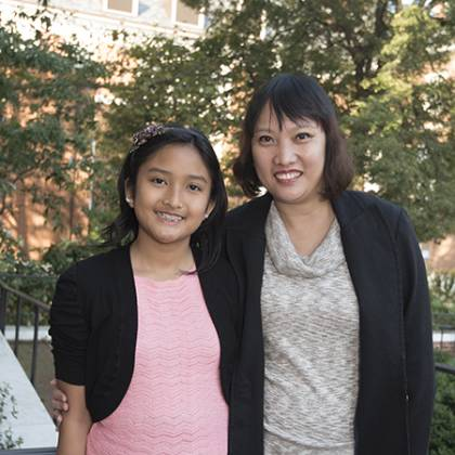 A girl in a pink shirt poses with her mother