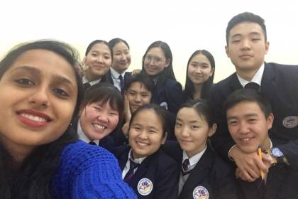 A woman takes a selfie with a group of students