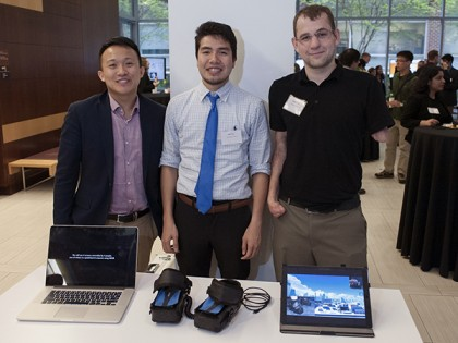 three students stand at a table displaying their design and two computers