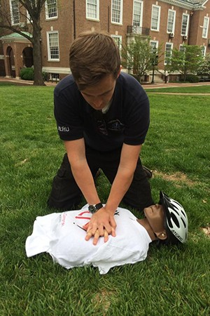 A student practices CPR maneuvers on a manikin