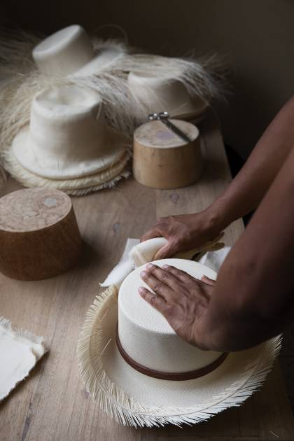 An artisan works with a nearly finished Panama hat