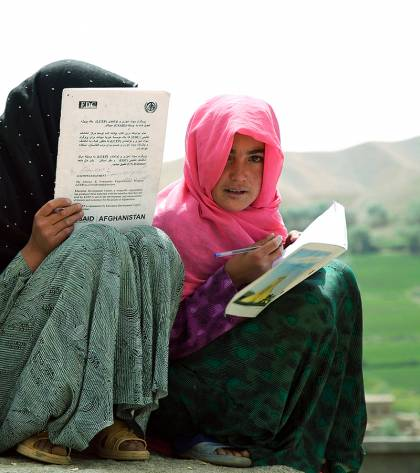 Two girls read study materials