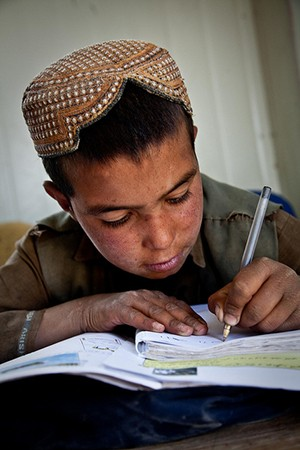 A boy leans over his open textbook and writes with a pen