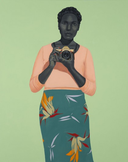 Portrait depicts a black woman holding a camera. Her skin is in a gray tone, and she's wearing a peach colored top and teal skirt with colorful cranes and birds of paradise on it; she stands against a mint green background.