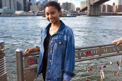 Girl wears jean jacker and smiles while her hand rests on a railing. The city and water is behind her. There are many padlocks on the fencing she leans against.