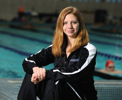 Swimmer Ana Bogdanovski sits next to pool in Johns Hopkins warmup suit