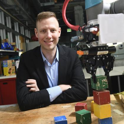 Andrew Hundt sits beside his block-stacking robot