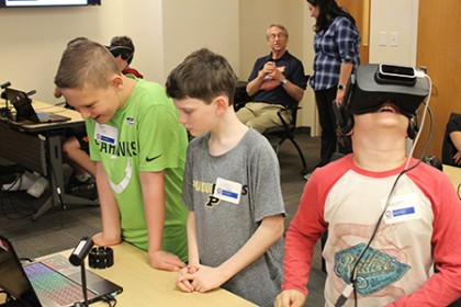 Two boys examine a computer screen while a third boy with VR goggles on his head looks up at the ceiling