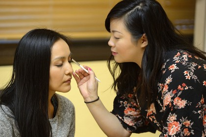 Teacher applies eyeshadow to student's face