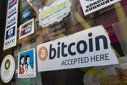 Photo shows a shop window plastered with stickers denoting forms of accepted payment, including a sign for Bitcoin
