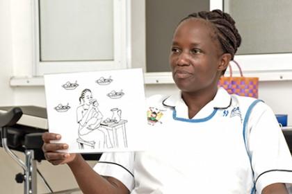 Lorna Othola, a nurse at Ahero Sub-County Hospital, displays a card showing a method of holding a breastfeeding baby
