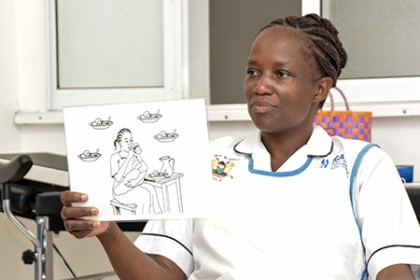 Lorna Othola, a nurse at Ahero Sub-County Hospital, displays a card showing a method of holding a breastfeeding baby