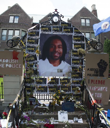 Picture of Philando Castile surrounded by flowers, protest signs