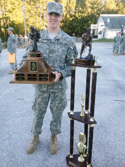 A man in military fatigues holds a trophy