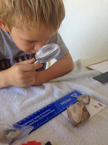 A little boy holds a plastic magnifying glass and inspects a rock that is laid out on a note card labeled with the number 4