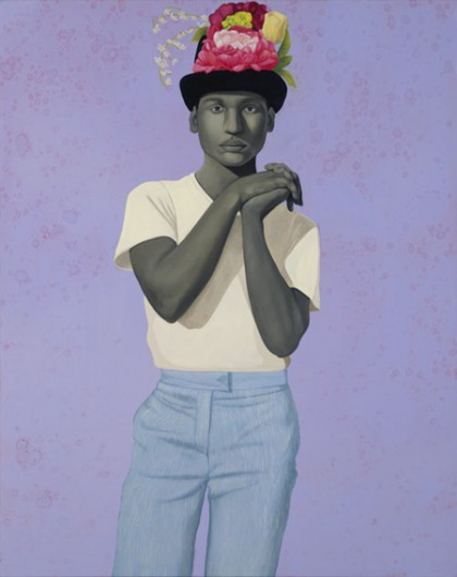 A man stares seriously out from this portrait; he clasps his hands with interlaced fingers and bends his left hand backwards; his skin is in a gray tone; he wears a white tee shirt and a color hat topped with flowers