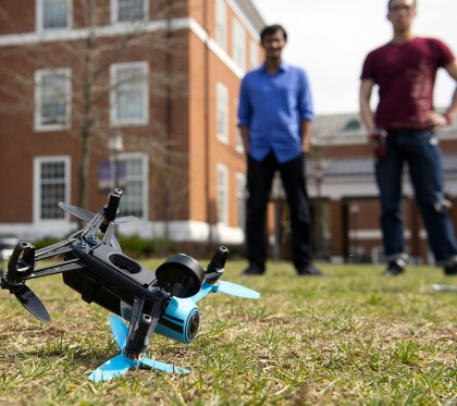 Two students stand in the background while a drone sits in the foreground