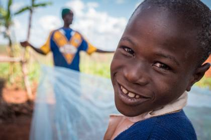 Alex and his father open a mosquito bed net that he received at school in Tanzania.
