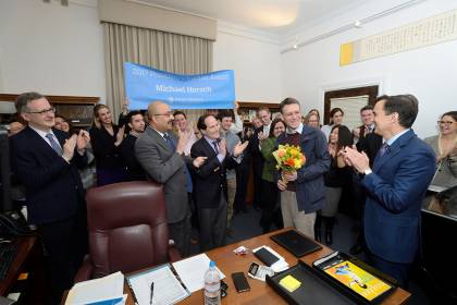 A crowd of people applaud a man standing in the center of the photo holding flowers