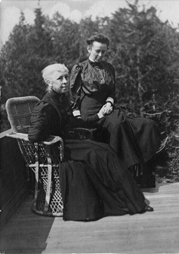 Grainy photograph shows two women, one on the left is sitting while the other stands beside her