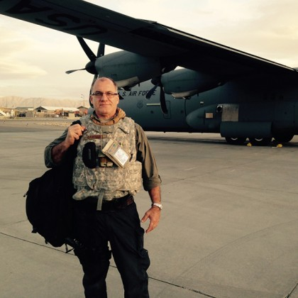 A man in a military flak vest holds bags in front of a Air Force plane