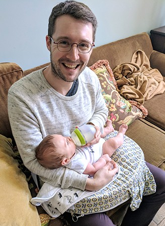 Man smiles while feeding baby from a bottle
