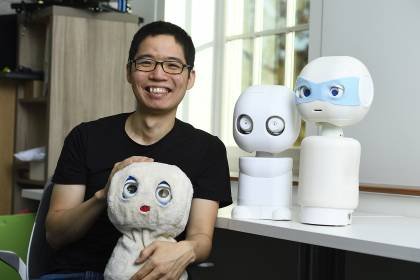 Chien-Ming Huang with the robots in his laboratory