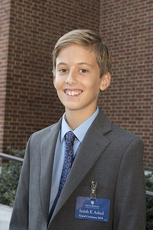 A young boy in a suit and tie smiles at the camera