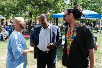 Three men speak at a festival