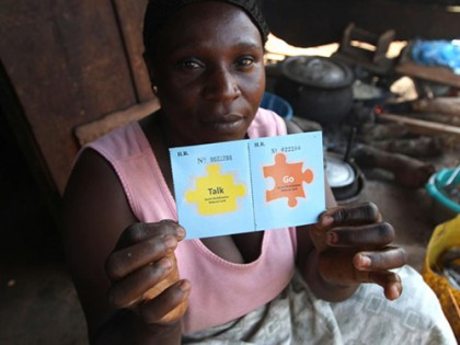 A woman holds two cards, one labeled
