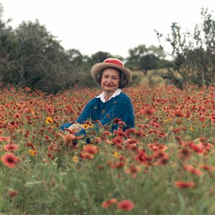 Lady Bird Johnson sits among a field of flowers