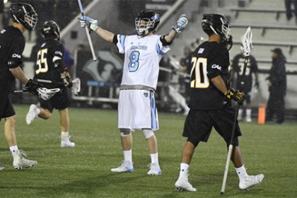 Hopkins player in white jersey raises both hands to celebrate goal