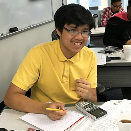 Student in yellow polo shirt poses for photo while working with notebook, calculator