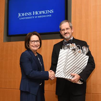 Janice Clements, vice dean for faculty, presents award to James Ficke, director of Orthopaedic Surgery