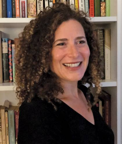 Photograph of Lizzie Skurnick standing in front of a bookshelf