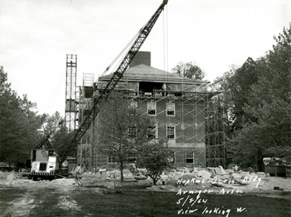 Black and white image of crane towering over brick campus building