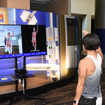 A woman views her musculoskeletal system on an interactive screen