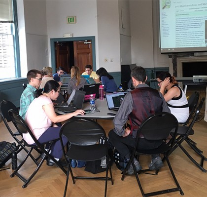 Map-a-thon participants work on laptops while sitting around round tables
