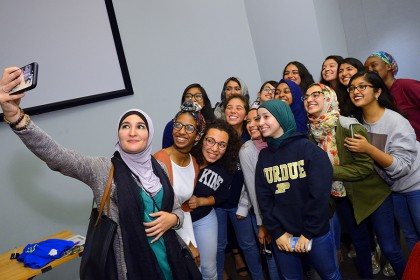 Linda Sarsour holds phone and takes selfie with group of about 15 students