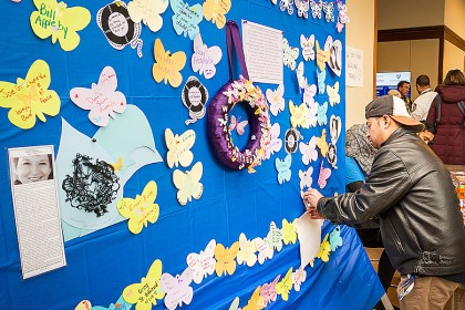 Names of people to be remembered are written on colorful butterflies on a memorial board