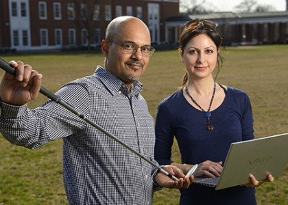Researchers pose with golf club, laptop computer