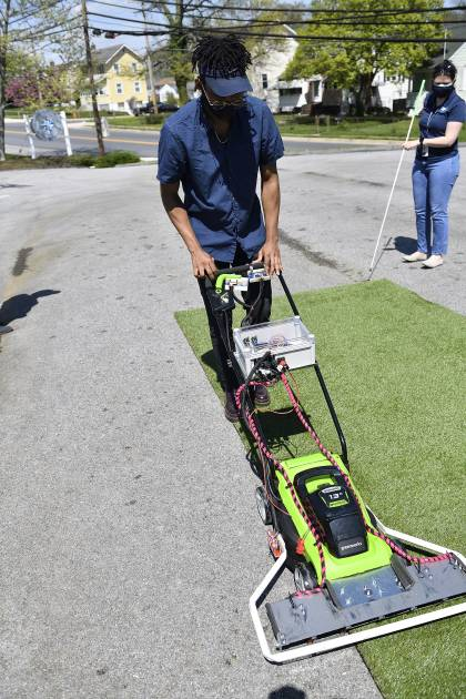 A student tests a modified lawnmower on astroturf