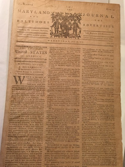 A yellowed parchment newspaper shows a published version of the Declaration of Independence
