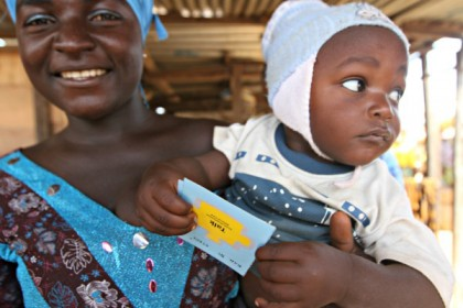 A woman holds a baby who is holding a card labeled