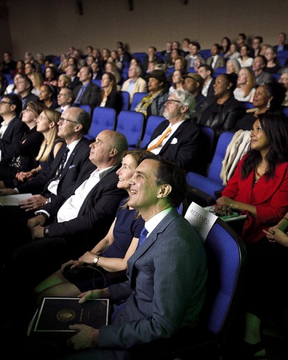 Guests sit in rows of blue seats at theater opening