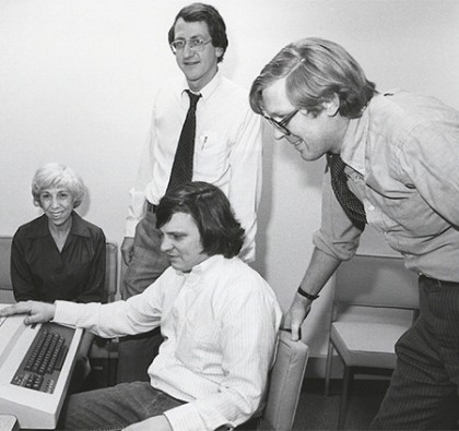 Black and white image of four people gathered around a computer