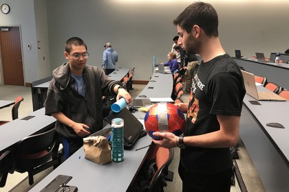 A student holds a soccer ball while another prepares a rolling object